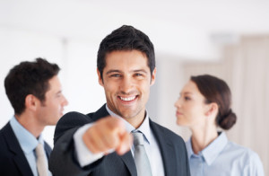 Smiling business man pointing at you with colleagues in background